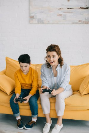 Photo for KYIV, UKRAINE - APRIL 8, 2019: Excited woman playing video game while sitting near offended son holding joystick - Royalty Free Image