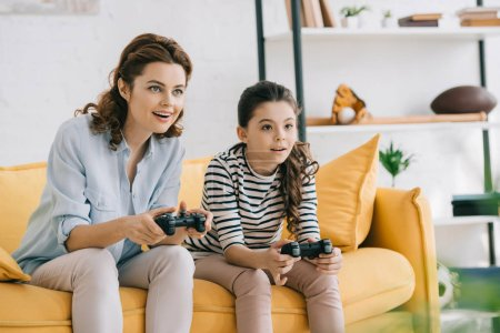 Photo for KYIV, UKRAINE - APRIL 8, 2019: Smiling mother and daughter playing video game while sitting on sofa at home - Royalty Free Image