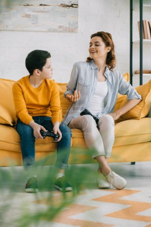 Photo for KYIV, UKRAINE - APRIL 8, 2019: Cheerful mother gesturing and looking at upset son holding joystick while sitting on sofa at home - Royalty Free Image