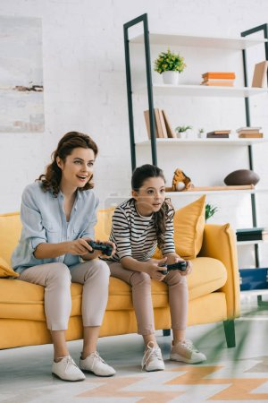 Photo for KYIV, UKRAINE - APRIL 8, 2019: Concentrated mother and daughter playing video game with joysticks while sitting on yellow sofa - Royalty Free Image