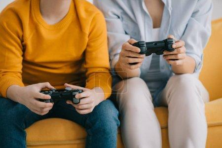 Foto de KYIV, UKRAINE - APRIL 8, 2019: Partial view of woman and boy holding joysticks and playing video game - Imagen libre de derechos