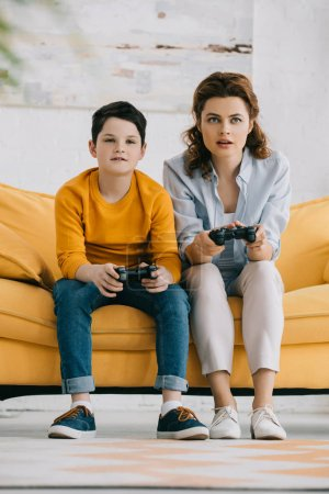 Photo for KYIV, UKRAINE - APRIL 8, 2019: Attentive mother and son playing video game with joysticks while sitting on yellow sofa - Royalty Free Image