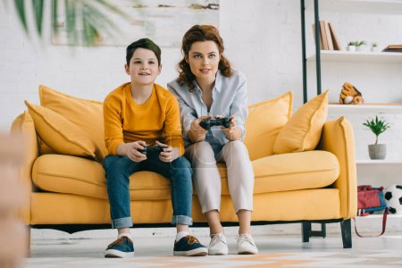 Photo for KYIV, UKRAINE - APRIL 8, 2019: Smiling mother and son playing video game with joysticks while sitting on yellow sofa - Royalty Free Image