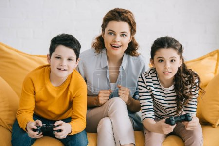 Photo for KYIV, UKRAINE - APRIL 8, 2019: Excited mother sitting on sofa near children playing video game with joysticks - Royalty Free Image