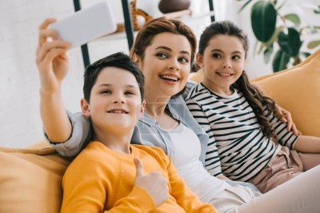 Photo pour Femme attirante heureuse prenant le selfie avec le smartphone tout en s'asseyant sur le sofa près du descendant et du fils de sourire - image libre de droit