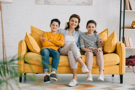Photo for Happy mother with cheerful children sitting on yellow sofa and looking at camera - Royalty Free Image