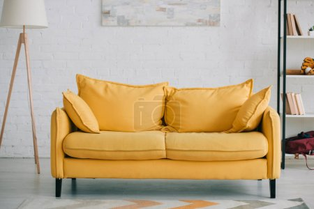 Photo pour Spacious, light living room with bright yellow sofa, floor lamp and rack - image libre de droit