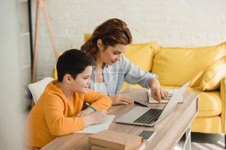 Photo pour Mère souriante aidant le fils attentif faisant le travail scolaire tout en s'asseyant au bureau avec l'ordinateur portatif à la maison - image libre de droit