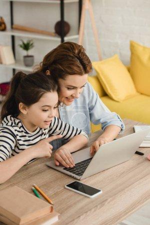 Photo pour Enfant surpris pointant avec le doigt tout en utilisant l'ordinateur portatif avec la mère - image libre de droit