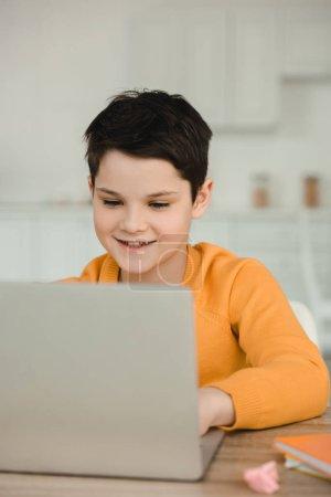 Foto de Sonriendo chico atento usando computadora portátil mientras hace tareas escolares en casa - Imagen libre de derechos