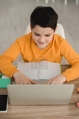 Photo pour Sourire concentré garçon en utilisant un ordinateur portable tout en étant assis au bureau avec copie livre et faire des travaux scolaires à la maison - image libre de droit