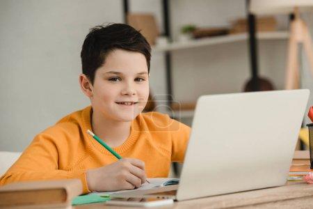 Photo pour Garçon souriant écrivant avec le crayon et regardant l'appareil-photo tout en faisant le travail scolaire à la maison - image libre de droit