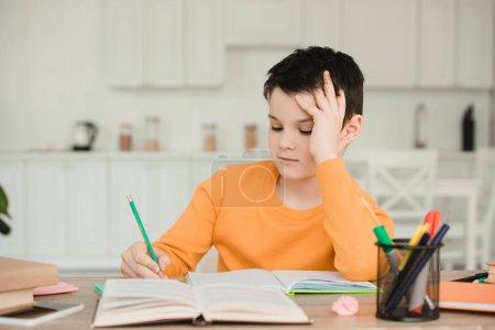 Photo pour Écolier attentif lecture livre et écriture tout en faisant des travaux scolaires à la maison - image libre de droit