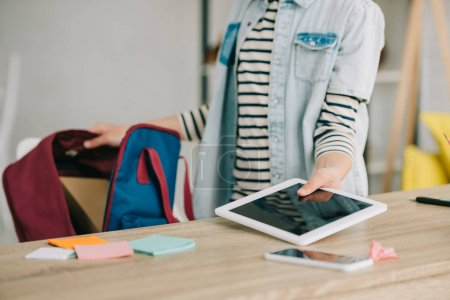 Photo for Cropped view of schoolchild holding digital tablet with blank screen while packing back pack - Royalty Free Image