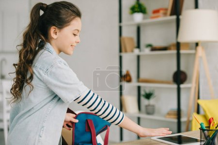 Photo for Cute schoolchild packing back pack while standing near desk with digital tablet with blank screen at home - Royalty Free Image