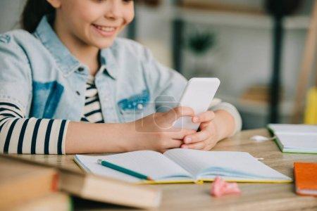 Photo pour Vue partielle de l'enfant de sourire utilisant le smartphone tout en s'asseyant au bureau et faisant le travail à la maison - image libre de droit