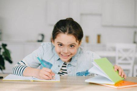 Photo pour Écolier gai souriant et regardant l'appareil-photo tout en faisant le travail d'école à la maison - image libre de droit