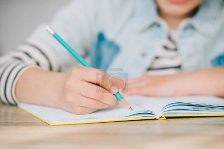 Photo for Partial view of schoolkid writing in copy book while doing homework - Royalty Free Image