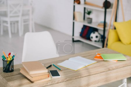 Photo for Selective focus of wooden desk with books, stationery, copy books and smartphone with blank screen - Royalty Free Image