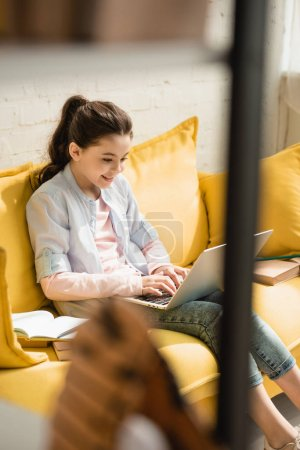 Photo for Selective focus of smiling child using laptop while sitting on sofa near books at home - Royalty Free Image