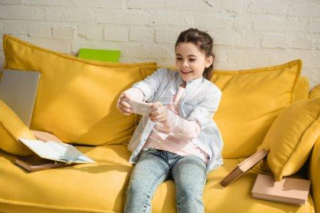 Photo pour Enfant gai prenant le selfie tout en s'asseyant sur le sofa jaune près des livres à la maison - image libre de droit