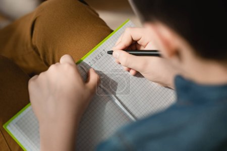 Foto de Enfoque selectivo de colegial escribir en libro de copia mientras se hace tareas escolares en casa - Imagen libre de derechos