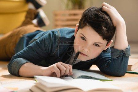 Foto de Enfoque selectivo de niño reflexivo acostado en el suelo cerca de copiar libro mientras que hacer tareas escolares en casa - Imagen libre de derechos