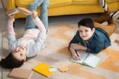 """Постер, картина, фотообои """"cheerful kids lying on floor at home and doing schoolwork together """""""