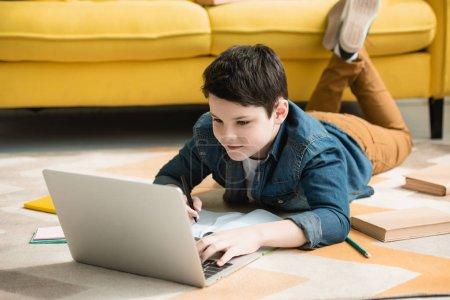 Photo pour Garçon attentif se trouvant sur l'étage près des livres et utilisant l'ordinateur portatif tout en faisant des devoirs - image libre de droit