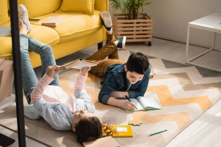 Photo for Adorable kids lying on floor at home and doing schoolwork together - Royalty Free Image