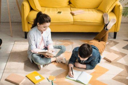 Foto de Vista de ángulo alto de niños adorables haciendo tareas escolares en el suelo en casa - Imagen libre de derechos