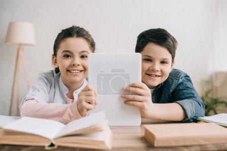 Photo pour Enfants gais retenant la tablette numérique et regardant l'appareil-photo tout en s'asseyant à la table avec des livres ensemble - image libre de droit