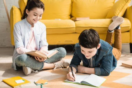 Photo for Adorable brother and sister doing schoolwork on floor at home together - Royalty Free Image