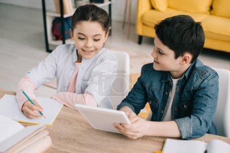 Foto de Adorable hermano y hermana sentado en la mesa y haciendo la tarea juntos en casa - Imagen libre de derechos