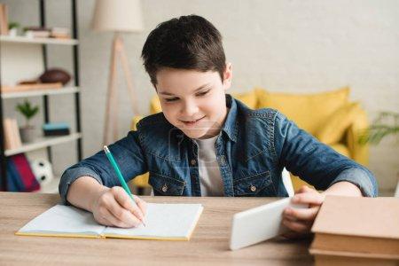 Photo pour Garçon souriant écrivant dans le cahier et utilisant le smartphone tout en faisant le travail scolaire à la maison - image libre de droit