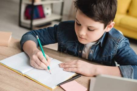Photo for Cute attentive boy writing in notebook while sitting at desk and doing homework - Royalty Free Image