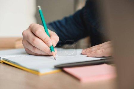 Photo pour Foyer sélectif de l'écriture d'écolier dans le cahier tout en faisant le travail d'école une maison - image libre de droit