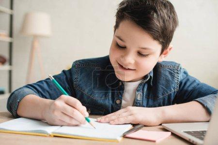 Photo pour Gai garçon écrit dans un carnet tout en étant assis au bureau et faire des devoirs - image libre de droit