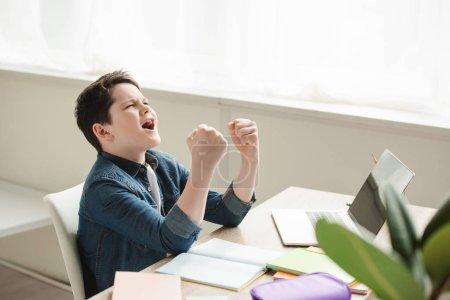 Photo pour Écolier excité montrant le geste de oui tout en s'asseyant au bureau et faisant des devoirs - image libre de droit