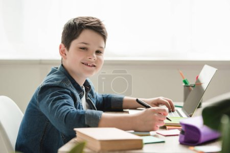 Photo for Cheerful boy looking at camera while sitting at table and doing homework - Royalty Free Image