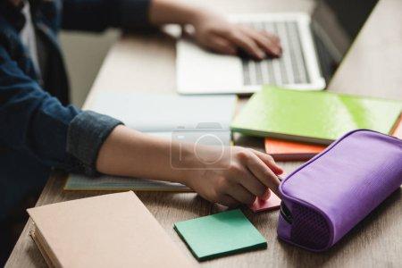 Photo pour Vue recadrée de l'écolier en utilisant un ordinateur portable tout en étant assis au bureau avec des livres de copie et de faire des devoirs - image libre de droit