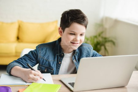 Foto de Cheerful boy writing in notebook and using laptop while doing schoolwork at home - Imagen libre de derechos