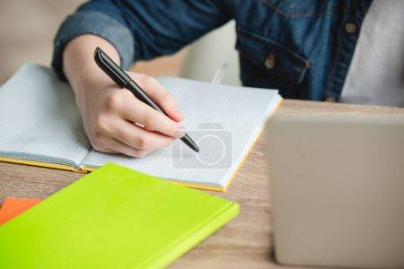 Photo pour Vue recadrée de l'écolier écrivant dans un cahier tout en faisant des travaux scolaires à la maison - image libre de droit