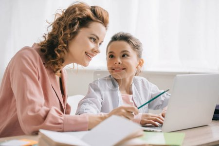 Photo for Happy mother pointing at laptop screen while helping daughter doing homework - Royalty Free Image
