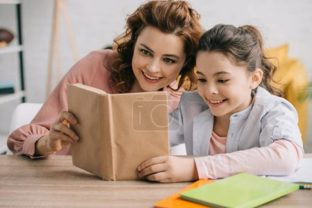 Photo for Happy mother and daughter sitting at wooden table and reading book together - Royalty Free Image