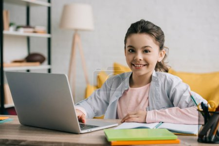 Photo for Happy child looking at camera while sitting at desk and using laptop at home - Royalty Free Image