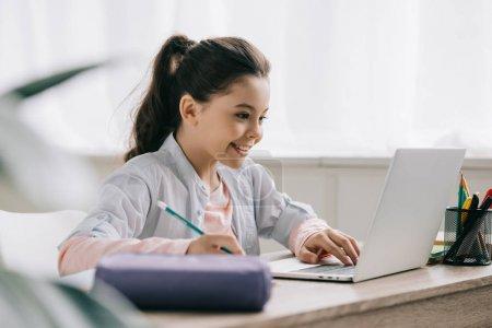 Photo pour Foyer sélectif de l'écriture joyeuse de l'enfant dans le carnet tout en faisant des devoirs - image libre de droit