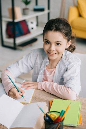 Photo pour L'écriture gaie de schoolkid dans le cahier et souriant à l'appareil-photo tout en faisant des devoirs - image libre de droit