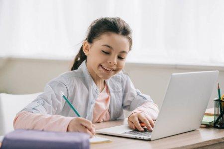 Photo pour Adorable enfant souriant écrivant dans le livre de copie et utilisant l'ordinateur portatif tout en faisant des devoirs - image libre de droit
