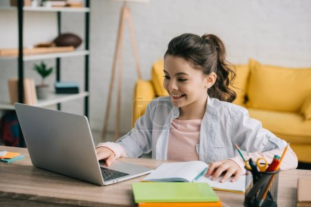 Photo for Cute smiling child using laptop while sitting at desk with copy books and doing homework - Royalty Free Image